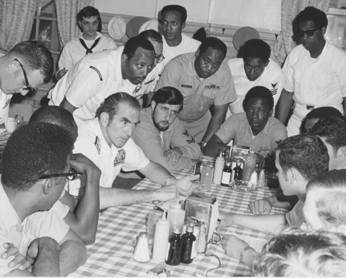 Admiral Zumwalt meeting with Sailors. Admiral Zumwalt and Sailors are seated at a table with other Sailors standing around the table.