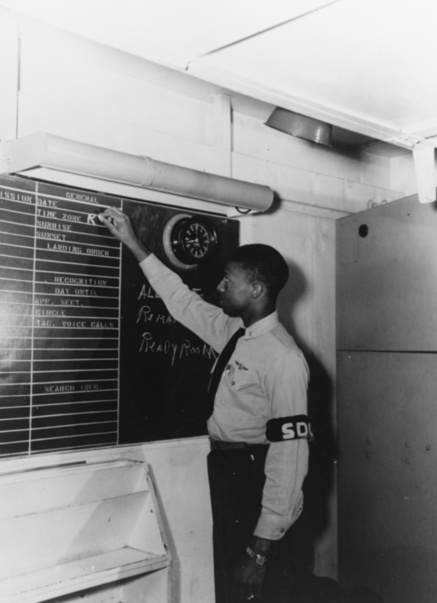 Ensign Jesse Leroy Brown, first African American to complete U.S. Navy flight training and the first African American naval aviator in combat and to be killed in combat, serves as squadron duty officer of VF-32, aboard USS Leyte (CV-32), 12 April 1949. (80-G-377909)