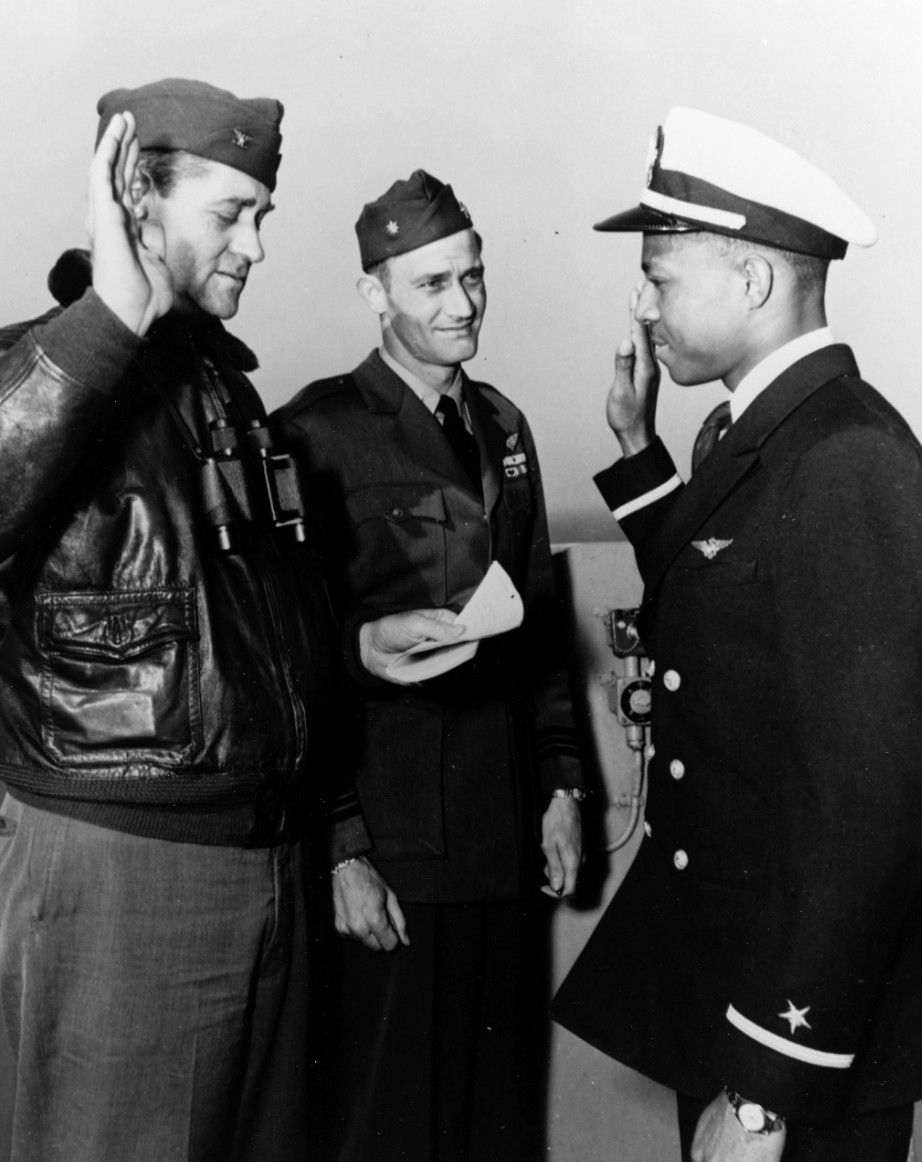 Ensign Jesse L. Brown, USN, Takes the oath of office on board USS Leyte (CV-32), 26 April 1949. Administering the oath is the ship's Commanding Officer, Captain William L. Erdmann. Lieutenant Commander E.D. Williams (center) is witnessing the ceremony. (80-G-707201)