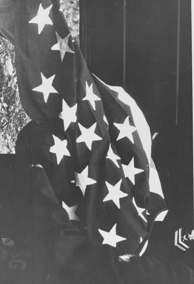 A Navy Yeoman Second Class holds a U.S. flag, to be used to drape the coffin of Seaman Duane Hodges. Click image to download.