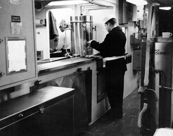 A crewmember draws a cup of coffee, in the crew's messing spaces, 1967.