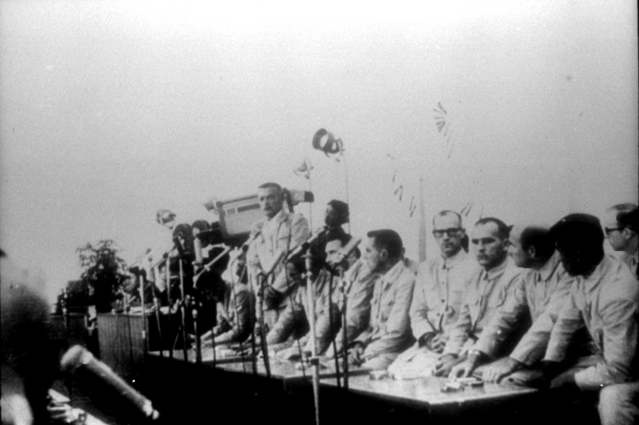Poor quality photograph of USS Pueblo (AGER-2) crewmembers at a press conference in North Korea. Click image to download.