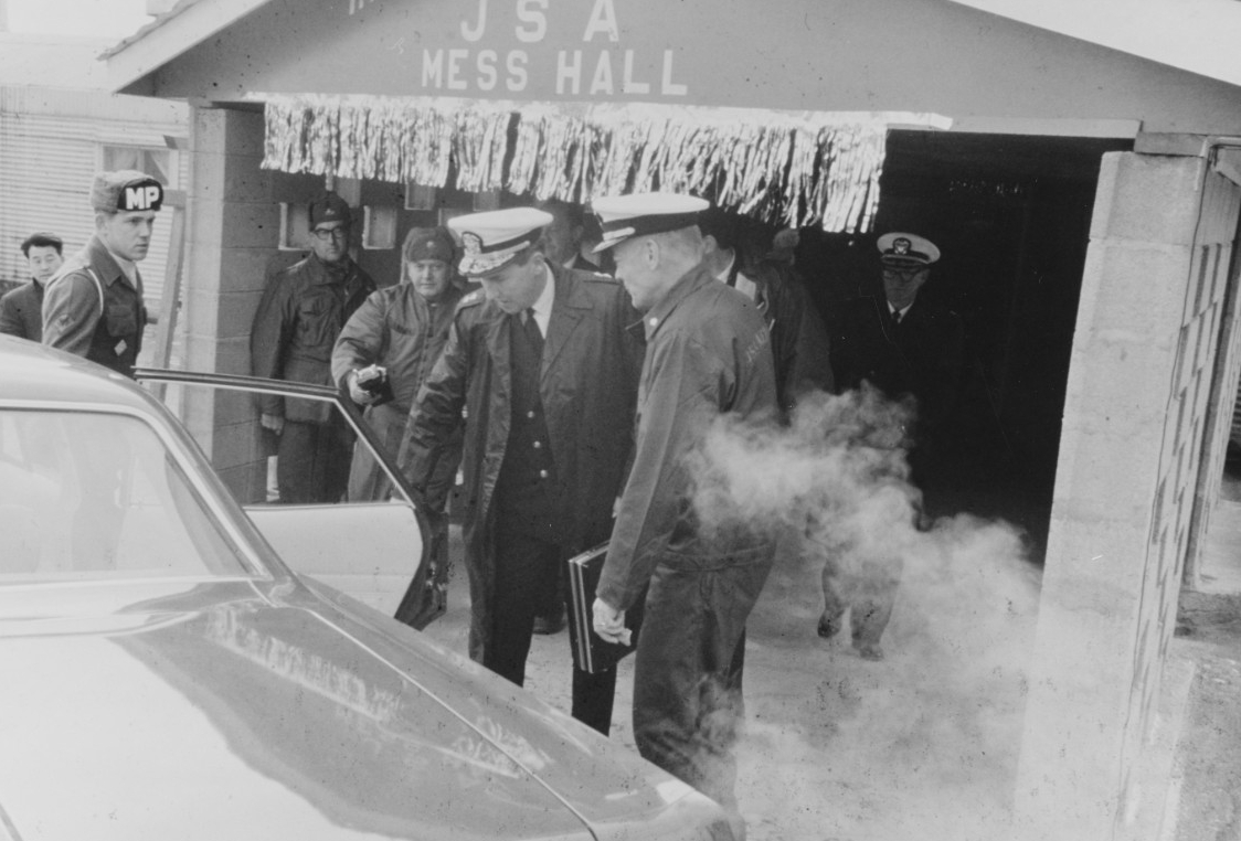 Rear Admiral Edwin M. Rosenberg, Commander Task Force 76 (center), and Commander Lloyd M. Bucher, Commanding Officer of USS Pueblo (AGER-2), enter an automobile as they leave the mess hall at the United Nations Advance Camp, Korean Demilitarized Zone, on 23 December 1968. Click image to download.