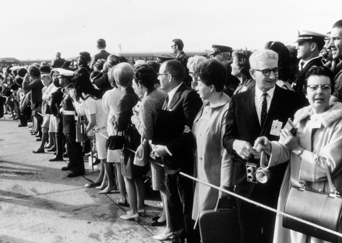 Families of the crewmembers of USS Pueblo (AGER-2) await the arrival of a plane bringing the men to Naval Air Station Miramar, California, 24 December 1968. Click image to download.
