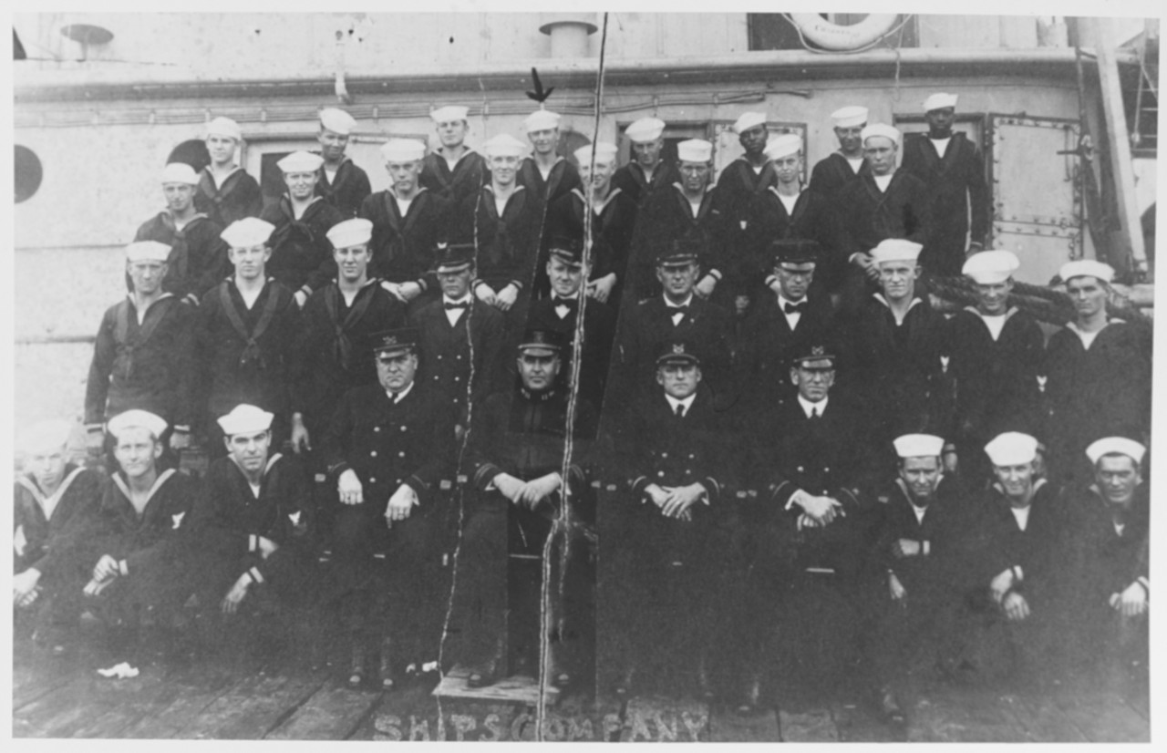 black and white photo of men standing in 4 rows on deck in front of ship in uniform