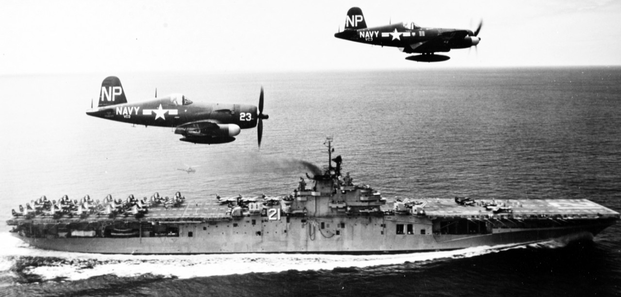 Aircraft carrier underway with two Corsair aircraft escorts.