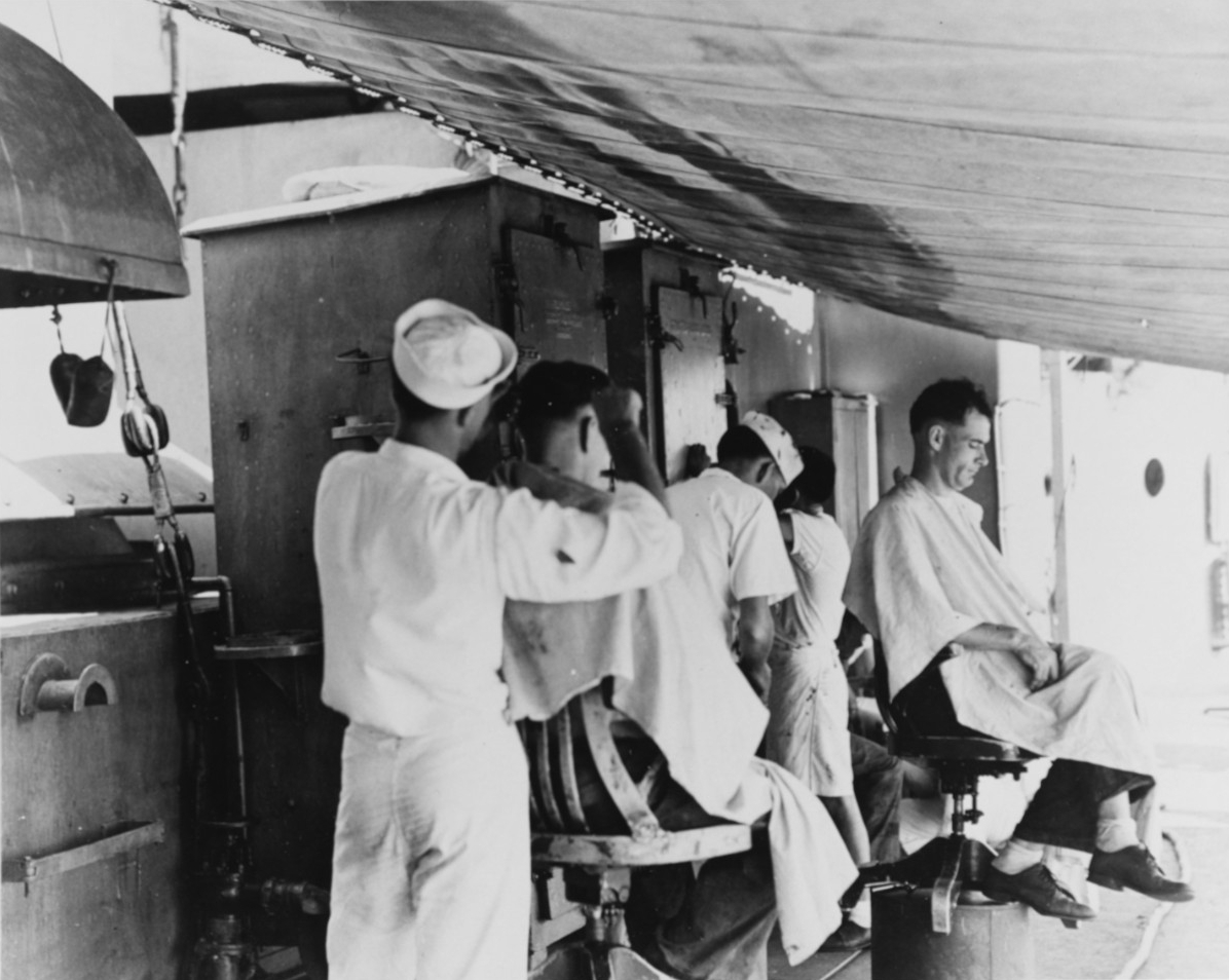 USS Marblehead (CL-12), view taken aboard ship in February 1942. Showing makeshift barbershop rigged up under an awning amidships. Shop belowdecks had been damaged during the air attack which heavily damaged the ship on 4 February 1942 in the Flores Sea.