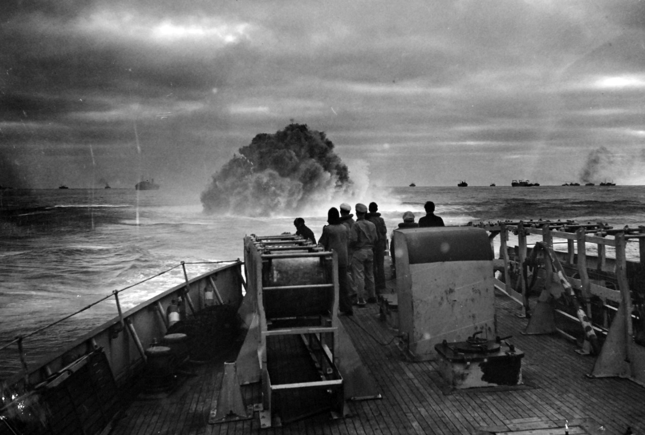 "26-G-1517:  Sinking of German submarine U-175, April  1943.   The submarine was sunk off south-west of Ireland by USCGC Spencer (WPG-36) on April 17, 1943.  Official Caption: ""COAST GUARD CUTTER SINKS SUB: Coast Guardsmen on the deck of the U.S. Coast Guard Cutter USCGC SPENCER (WPG-36) watch the explosion of a depth charge which blasted a Nazi U-Boat's hope of breaking into the center of a large convoy.  The depth charge tossed from the 327-foot cutter blew the submarine to the surface, where it was engaged by Coast Guardsmen.  Ships of the convoy may be seen in the background.""  Date: 17 April 1943.  Official U.S. Coast Guard Photograph, now in the collections of the National Archives.  (2017/09/05)."