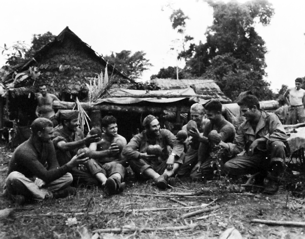 "127-GW-966-77431:  Battle of Cape Gloucester, New Britain, December 1943-January 1944 ""Birthday Toast"".   A toast if drunk in coconut juice on the occasion of the 24th birthday of Sergeant Milan A. Cicak, USMC.  The birthday found him and his buddies on a patrol in the Cape Glouchester jungle.  That's Cicak in the center.  Left to right:  Gunnery Sergeant William E. Eisenhower; Private First Class Dominik D. Garogano.   Official U.S. Marine Corps Photograph, now in the collections of the National Archives.   (2014/7/9)."
