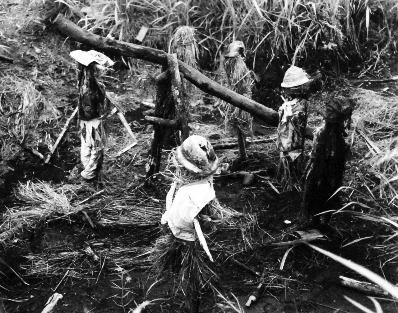 127-GW-970-71518:   Battle of Cape Gloucester, New Britain, December 1943-January 1944.  Dummy Japanese gun crew.   To make Marines think the enemy was strong in one section on Cape Gloucester, the Japanese rigged up this scarecrow gun and crew. Photographed by Howard, 15 January 1944.  Official U.S. Marine Corps Photograph, now in the collections of the National Archives.   (2014/7/9).