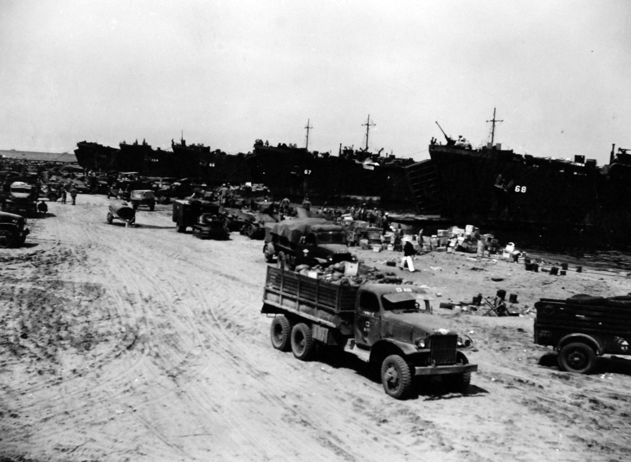 80-G-57458:  Battle of Cape Gloucester, New Britain, December 1943-January 1944.  Supplies being unloaded on the beachhead by LST-66, LST-67, LST-68, LST-202, and LST-204. Photographed by USS Nashville (CL-43), December 24-26, 1943.   Official U.S. Navy Photograph, now in the collection of National Archives (2018/04/25).