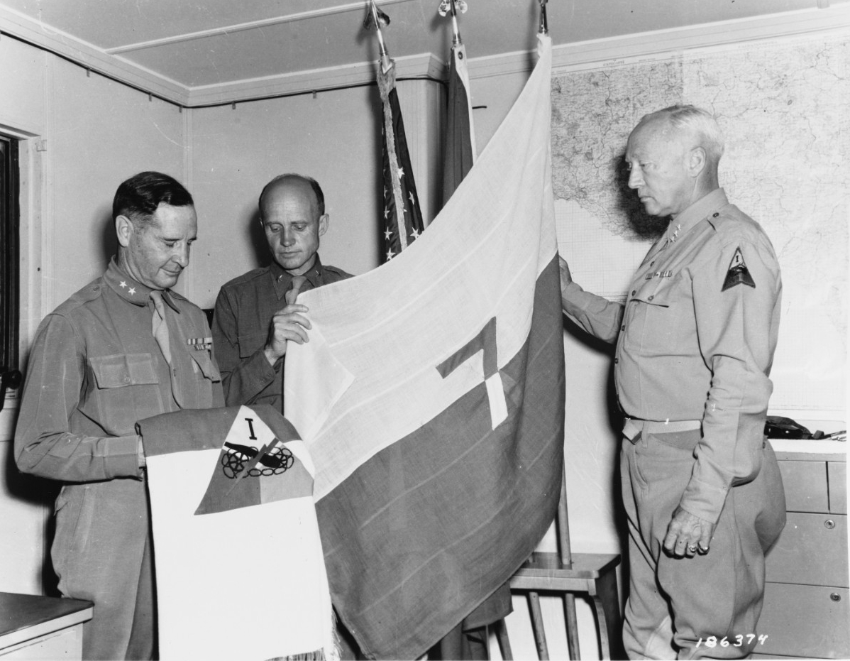 Sicily Invasion, July 1943. Major General Geoffrey Keyes, Brigadier General Hobart Gay, Lieutenant General George S. Patton, CG, 7th Army examining a 7th Army flag.