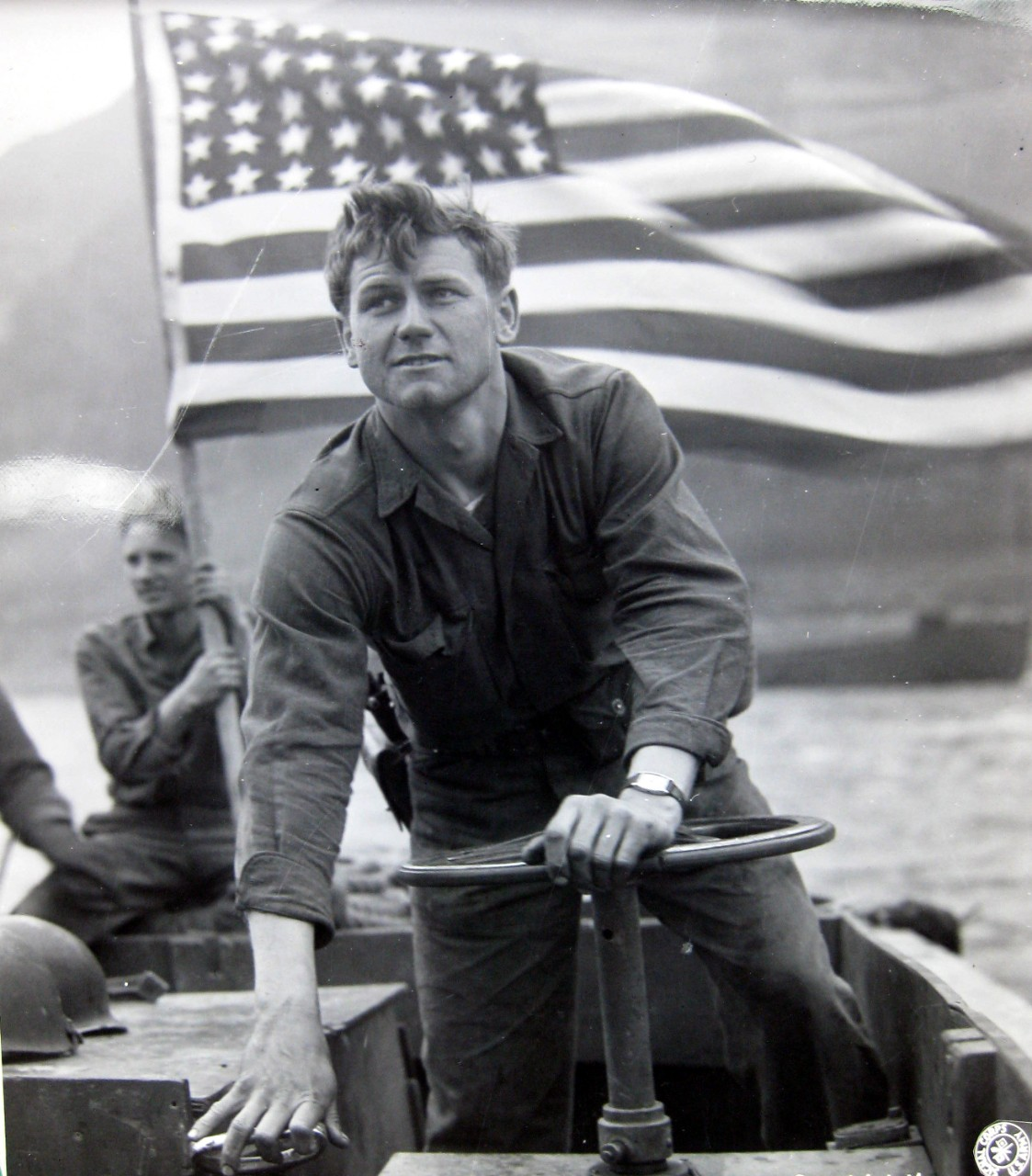 <p>With the American flag flying over his head, Motor Machinist's Mate Robert Mooty, USN, ferries troops across the Rhine River at Oberwesel, Germany.</p>