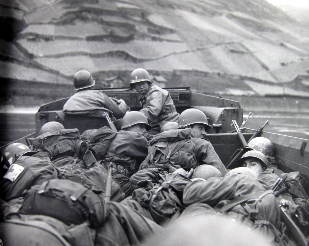 <p>Crouching low for concealment and protection in a DUKW amphibious vehicle, men of the 89th Division, U.S. Third Army, cross the Rhine River at Oberwesel, Germany.</p>