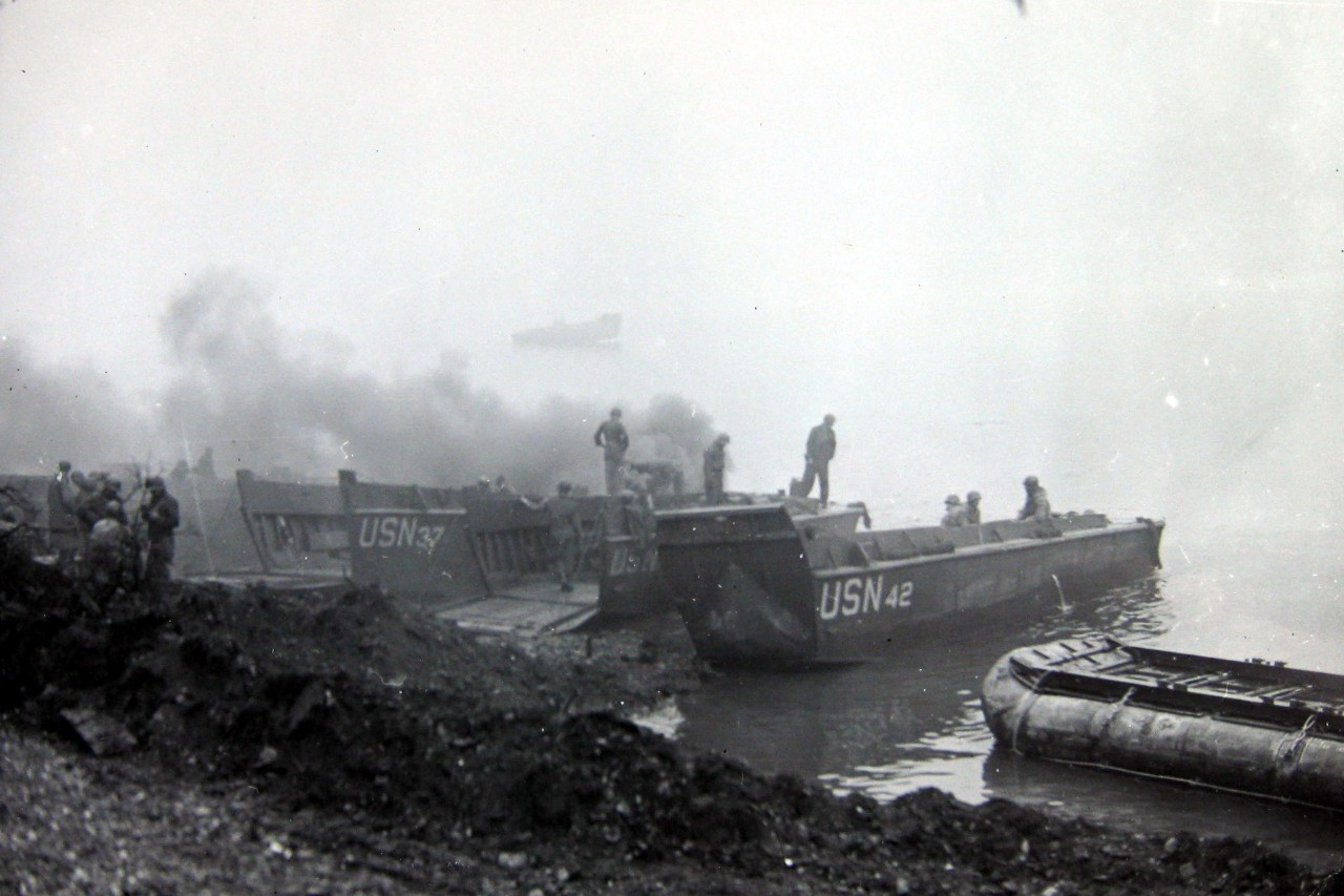 <p>Equipment is loaded on Navy LCVP boats to be ferried across the Rhine River.</p>