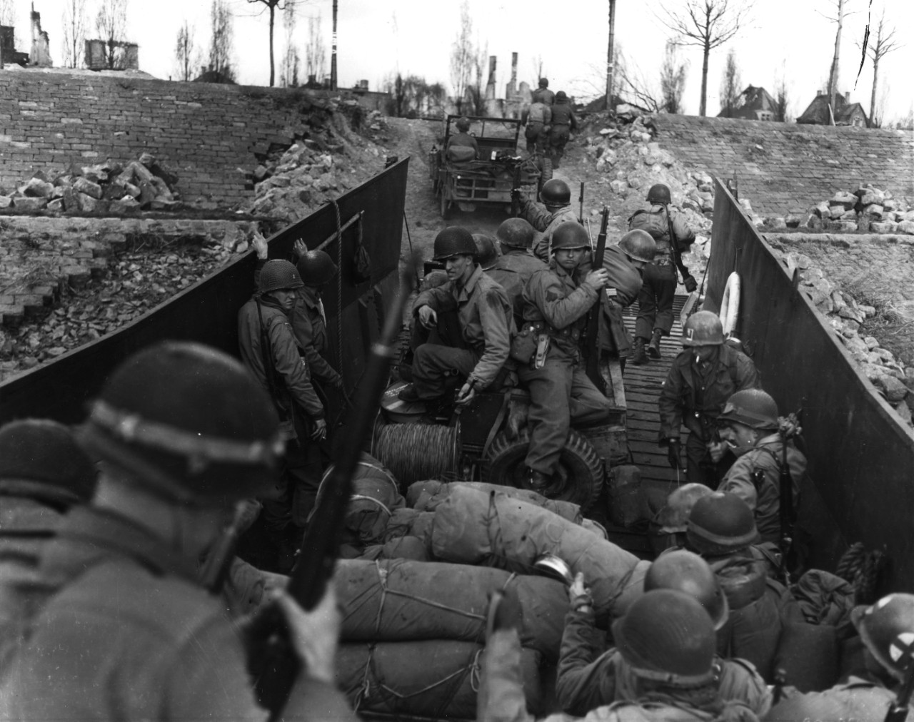 <p>Men and vehicles of the 80th Infantry Division, Third US Army, load into a landing craft prior to crossing the Rhine River, Germany, 29 March 1945. Note M-1 Garand rifle and belt gear of man in center, including TL-29 knife, and M-1 carbines carried by other men.</p>