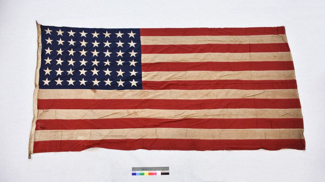 "<p></p><p style=""margin: 0in 0in 8pt;"">One forty-eight-star national ensign from the escort aircraftcarrier USS Thetis Bay (CVE-90). The flag is cotton, of sewn construction and rectangularin shape. Seven alternating horizontal stripes of red and white are joined to ablue canton in the top left corner. Forty-eight individually applied white starsare sewn to each side of the canton. There is a rope running through the whitehoist which extends out from the top and bottom and is folded back at each endto form loops. The hoist is stamped in black with manufacturing information anddimensions.</p><div style=""left: -10000px; top: 0px; width: 9000px; height: 16px; overflow: hidden; position: absolute;""><div>&nbsp;</div></div>"