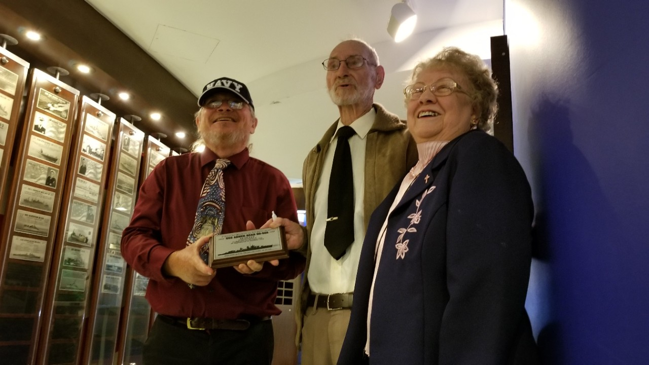 Three people hold the plaque of the USS Abner Read dedication ceremony