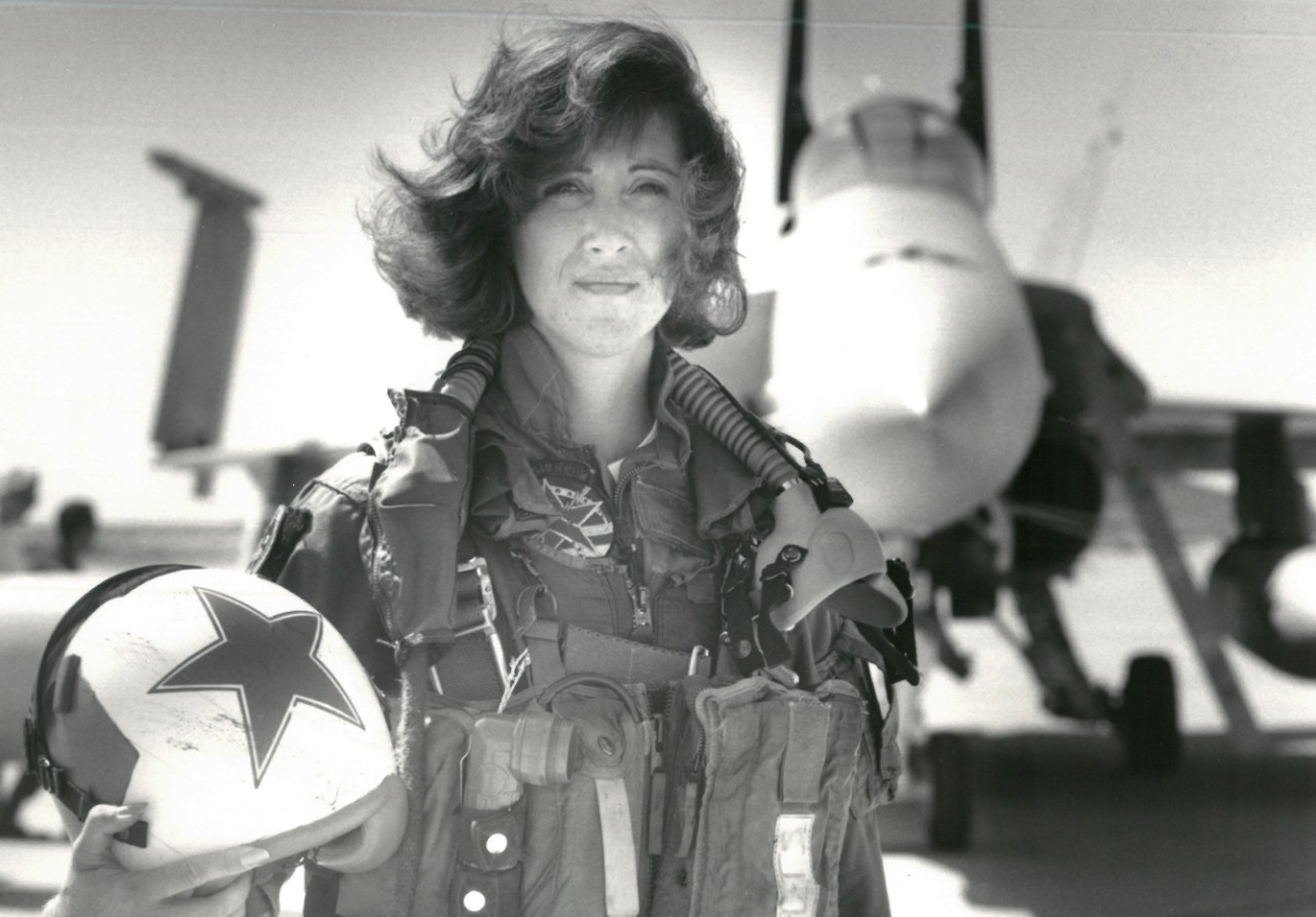 Female U.S. Navy pilot standing in front of an F/A-18A with helmet in hand.