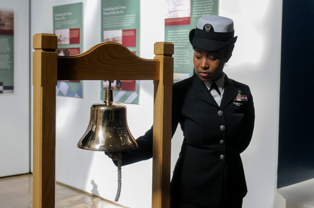 Mass Communication Specialist 2nd Class Destiny Cheek rings a bell during a Bell Ringing ceremony for the USS San Diego exhibit