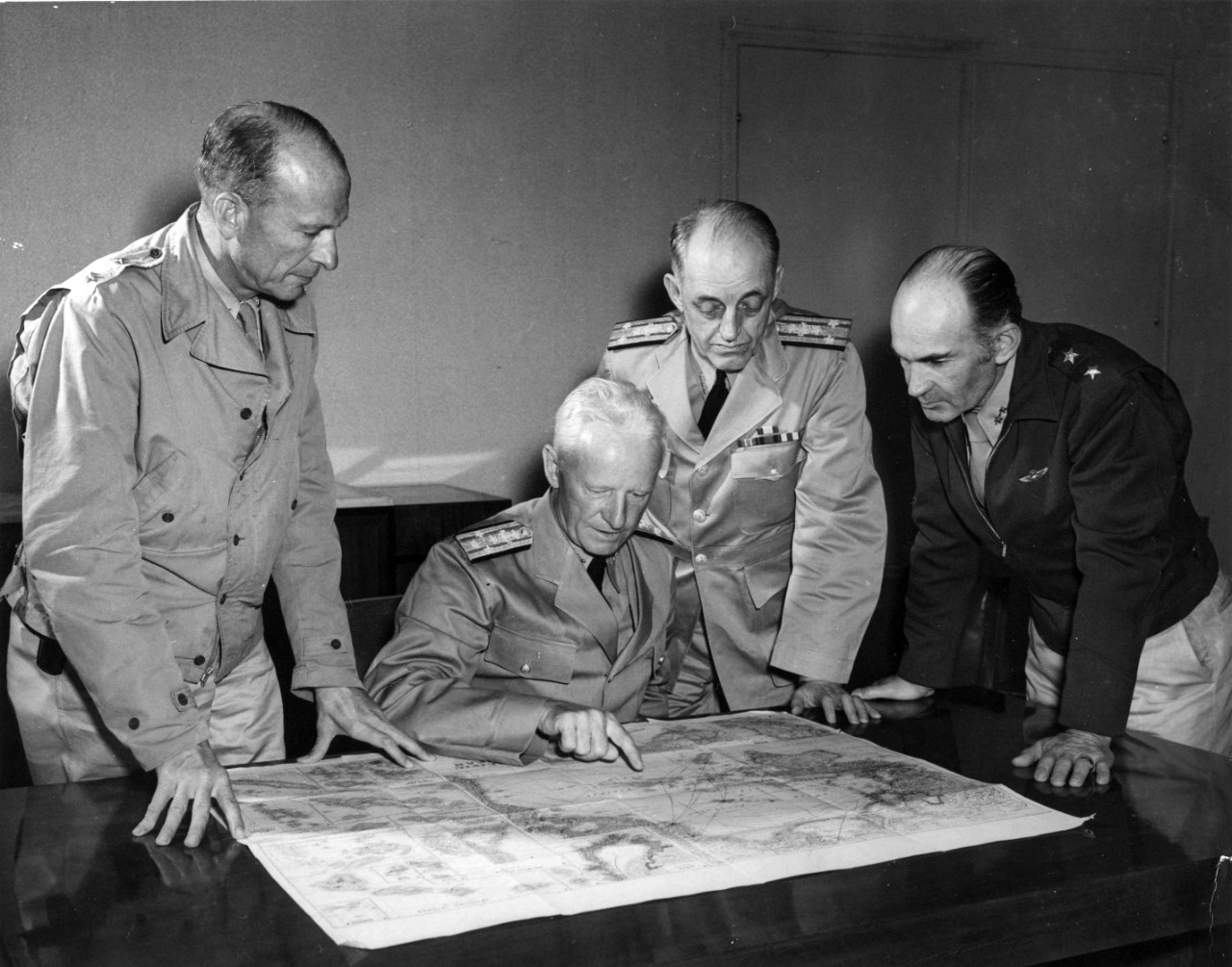 Admiral Chester W. Nimitz, USN, Commander in Chief Pacific Fleet and Pacific Ocean Areas confers with south Pacific area officers, possibly aboard USS Argonne (AG-31) at Noumea, New Caledonia, on 28 September 1942.