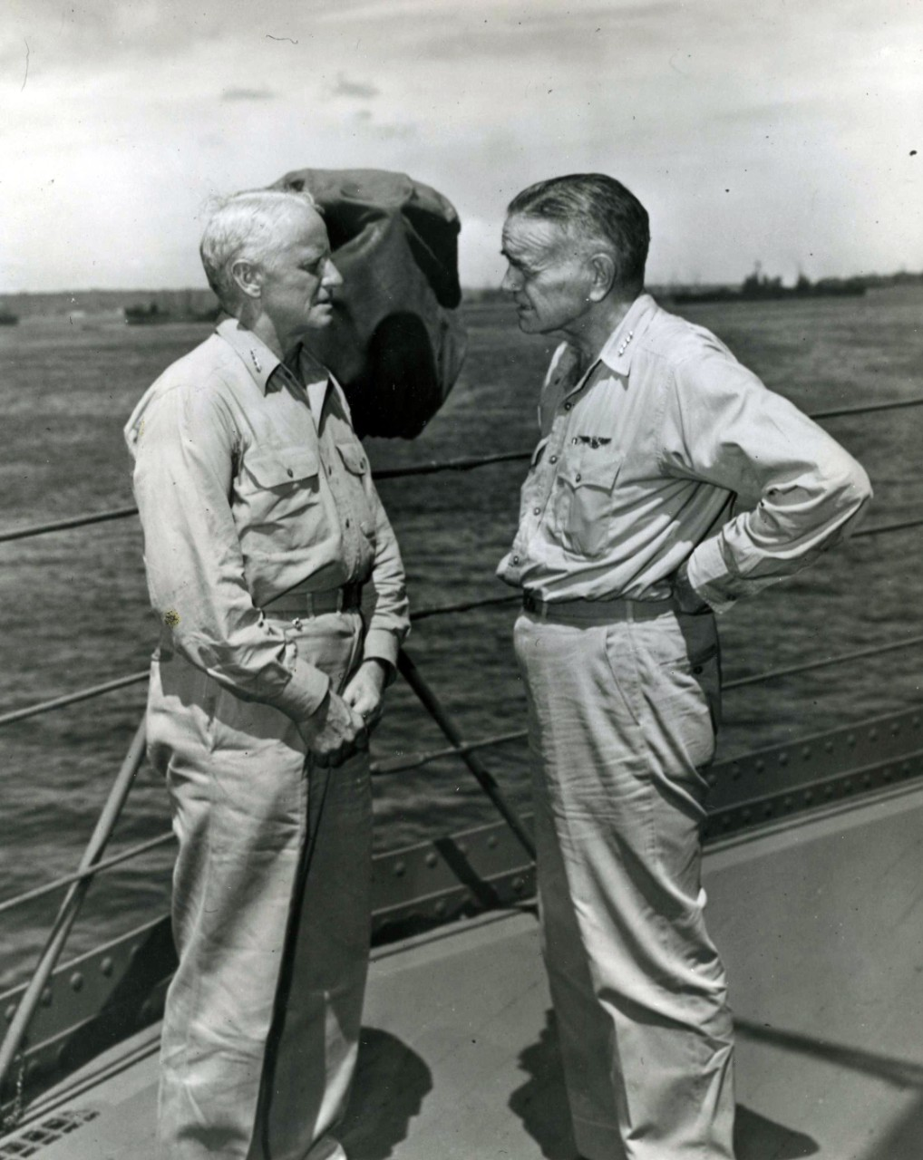 "Admiral Chester W. Nimitz, USN, Commander in Chief Pacific and Pacific Ocean Areas (left), and Admiral William F. Halsey, USN, Commander, South Pacific Area and South Pacific Force, confer aboard USS Curtiss (AV-4) at ""Button"" Naval Base, Espiritu Santo, New Hebrides, 20 January 1943."