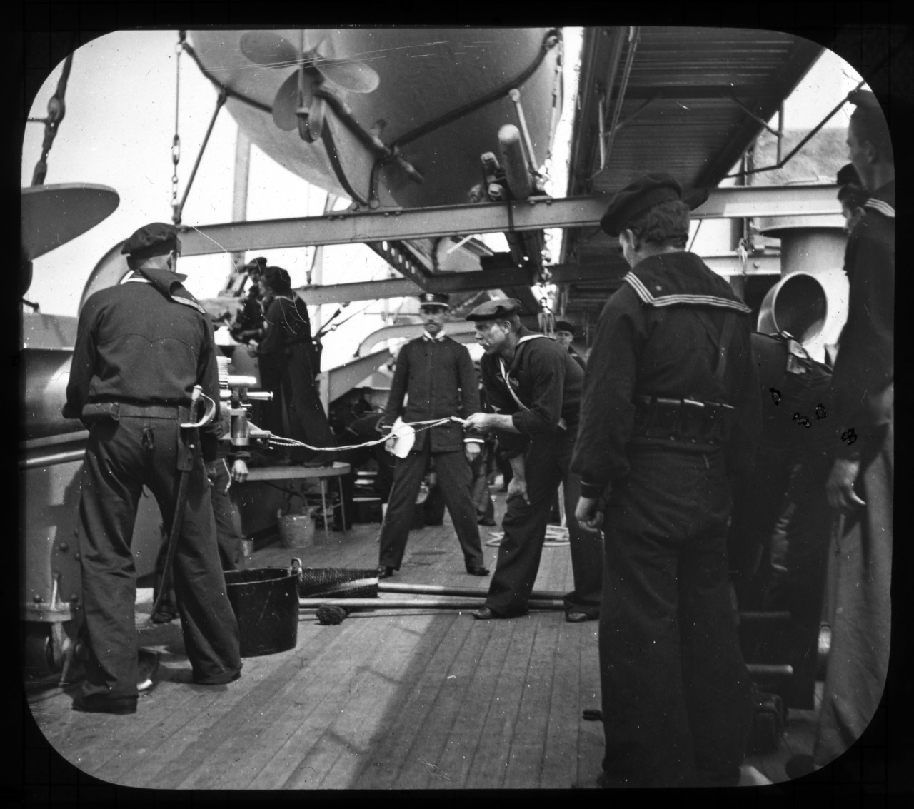 An undated photo shows Sailors of USS Charleston (C-2) manning one of the ship's guns during the Spanish-American War. Naval History and Heritage Command photo archives staff members are scanning a wooden box containing approximately 150 glass plate photographs depicting scenes from the Spanish-American and Philippine Wars.