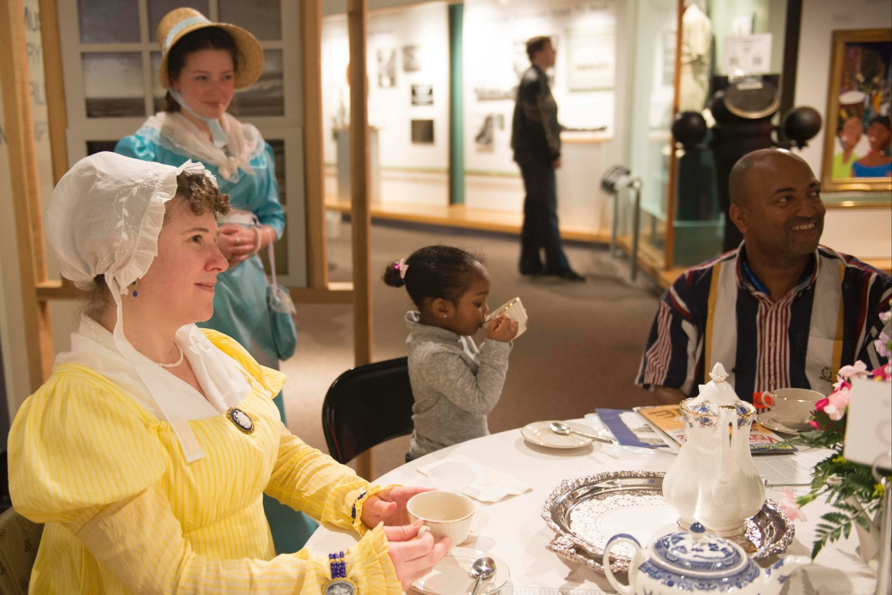 Period re-enactor Stacy Weissner, from the Virginia Regency Society, drinks tea with Leia Palmer, 3, during the Hampton Roads Naval Museum's tea party