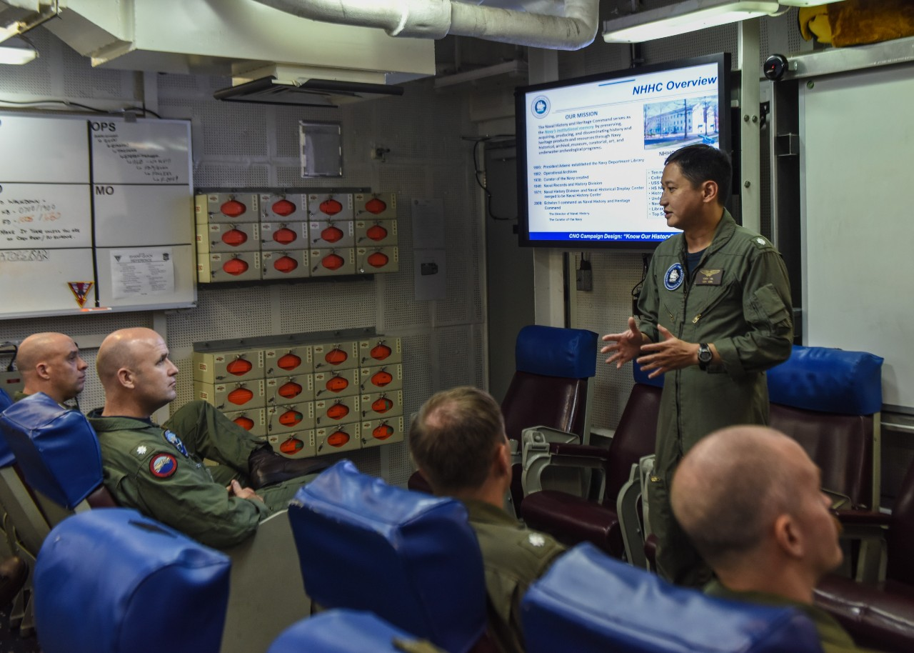 Cmdr. Eddy Ha, chief of staff for Navy History and Heritage Command, gives a brief to staff from Helicopter Maritime Strike Squadron (HSM) 77