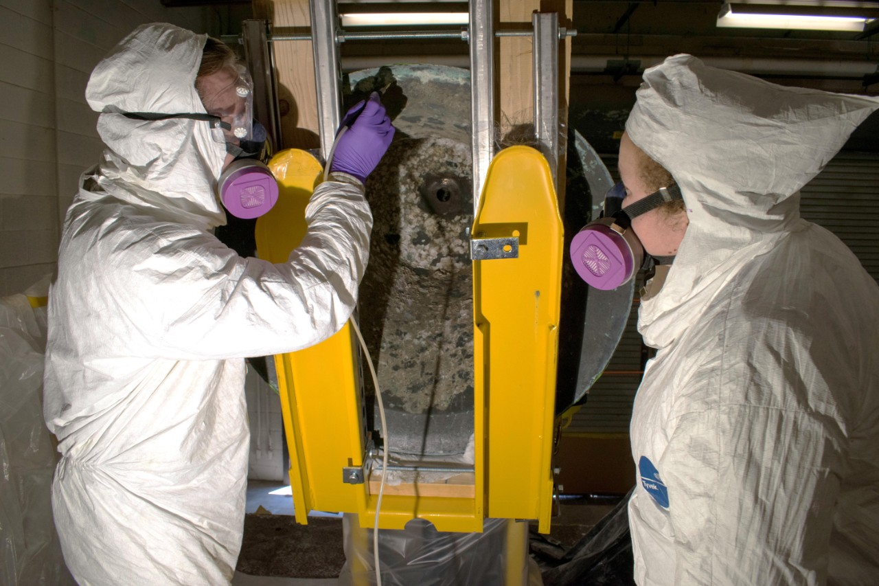 Melissa Swanson and Karl Knauer, conservators at Naval History and Heritage Command, conduct micro abrasive cleaning treatments on the underside of the USS Utah bell's rim. (U.S. Navy photo by Naval History and Heritage Command Collection Management Facility staff/Released)