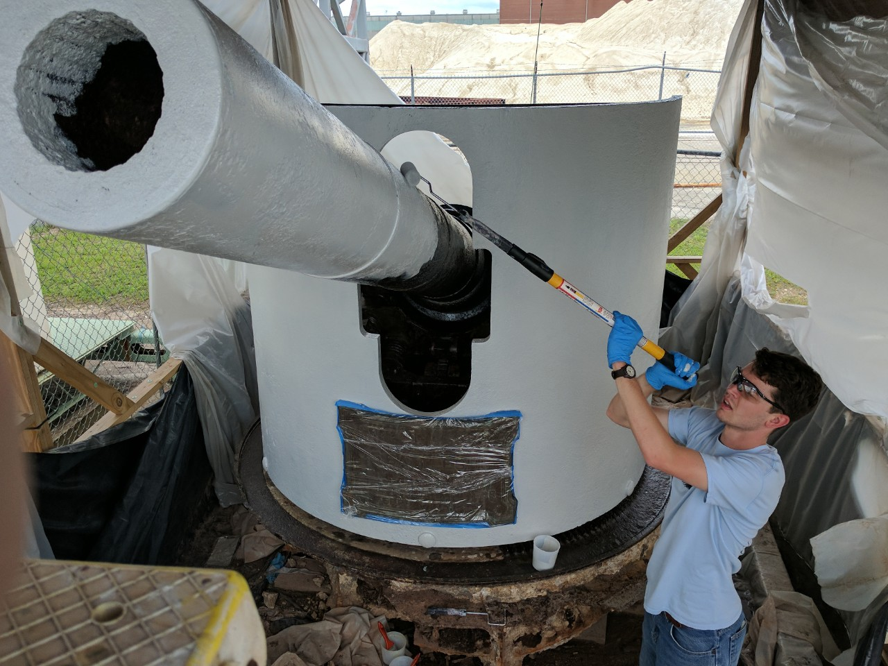 Young man painting primer on a large naval gun