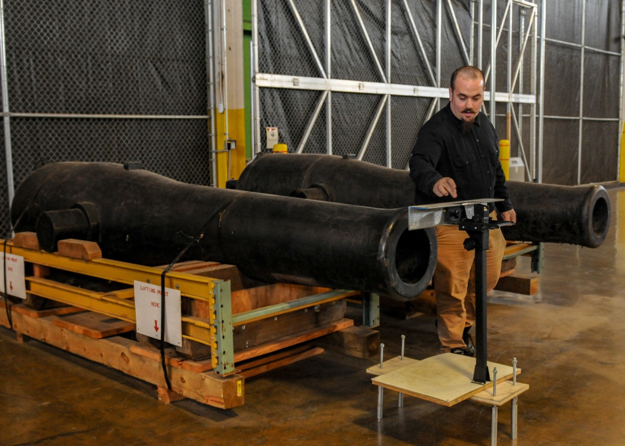 archaeological conservator from the Mariners' Museum and Park located in Newport News, works with a device to collect measurement data from a Dahlgren smoothbore shell gun from Kearsarge I (Sloop-of-War)