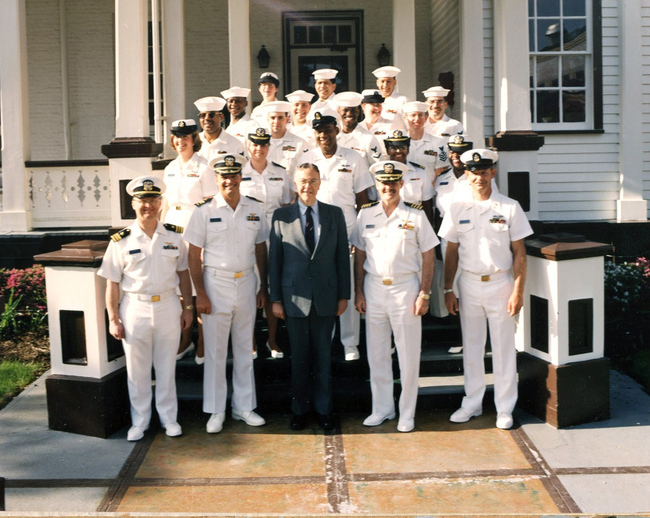 Dr. Dean Allard pictured (center) on the Washington Navy Yard in an undated photo with several Sailors in their dress whites. Dr. Allard was the Naval History Director from 1989-1995.