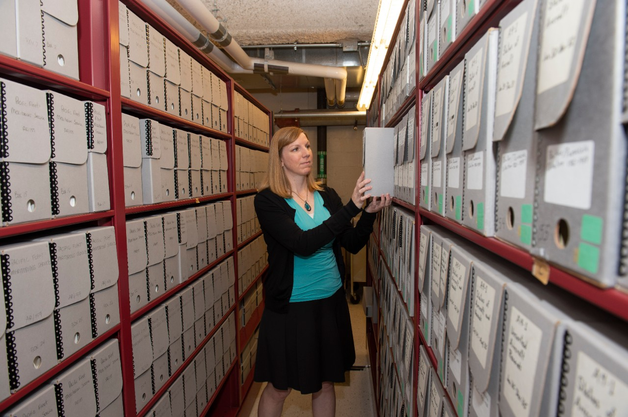 <p>Laura Waayers, a reference archivist at the Navy History and Heritage Command (NHHC) pulls command operations reports from the Navy archives.</p>