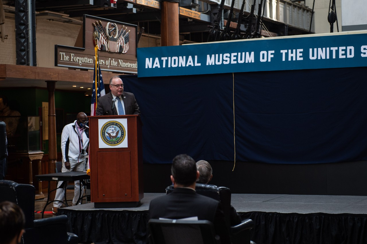 Retired Rear Adm. Sam J. Cox, Director, Naval History and Heritage Command (NHHC), gives a speech during the announcement ceremony of the new National Museum of the United States Navy (NMUSN) in the current NMUSN. To honor the service of American Sailors and enhance the public understanding of the Navy's history and heritage, the Navy is creating a new NMUSN. NHHC, located at the Washington Navy Yard, is responsible for the preservation, analysis, and dissemination of U.S. naval history and heritage.
