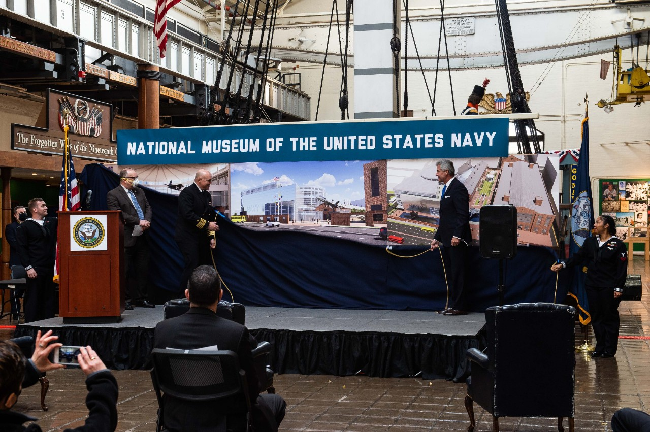 Secretary of the Navy, Kenneth J. Braithwaite and members of Naval History and Heritage Command (NHHC) unveil renderings of the future National Museum of the United States Navy (NMUSN) during the announcement ceremony of the new NMUSN. To honor the service of American Sailors and enhance the public understanding of the Navy's history and heritage, the Navy is creating a new NMUSN.