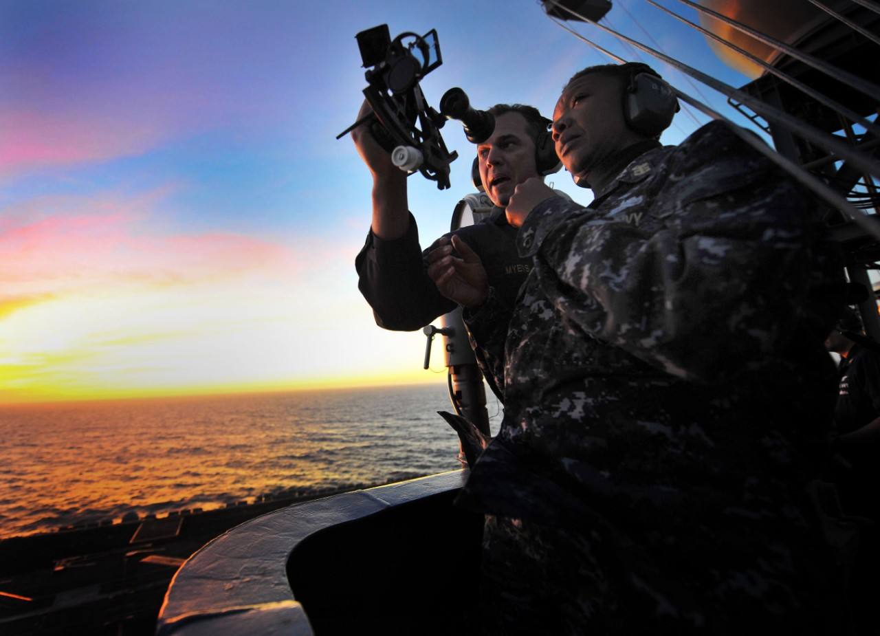 Senior Chief Petty Officer Jonathan Myers teaches Command Master Chief April Beldo how to use a marine sextant during a demonstration of celestial navigation aboard the aircraft carrier USS Carl Vinson (CVN 70)
