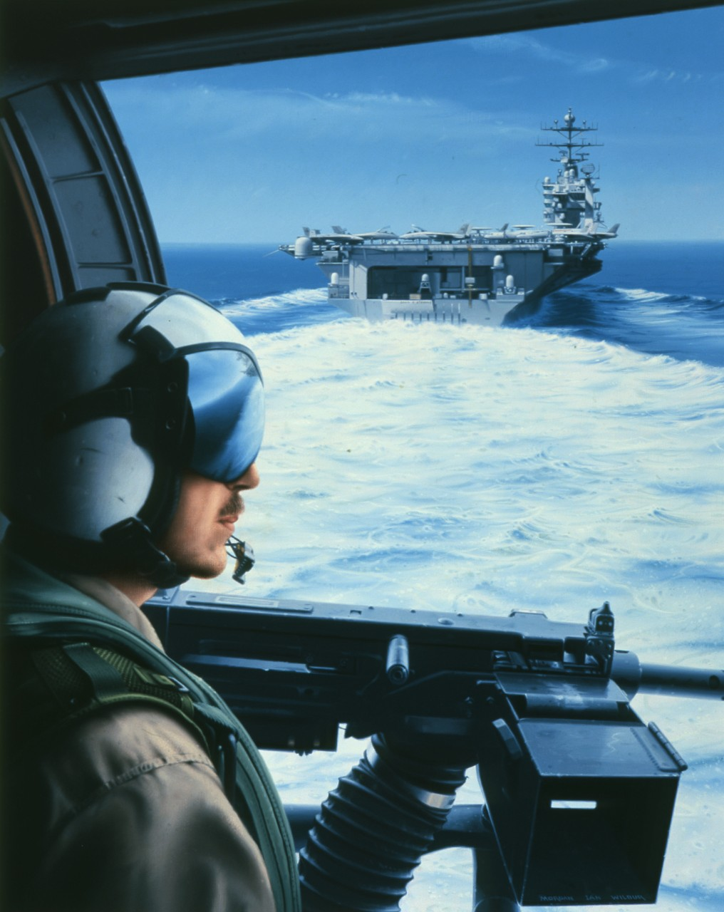 A crewman looks out the hatch of a helicopter, he is looking at the stern of an aircraft carrier