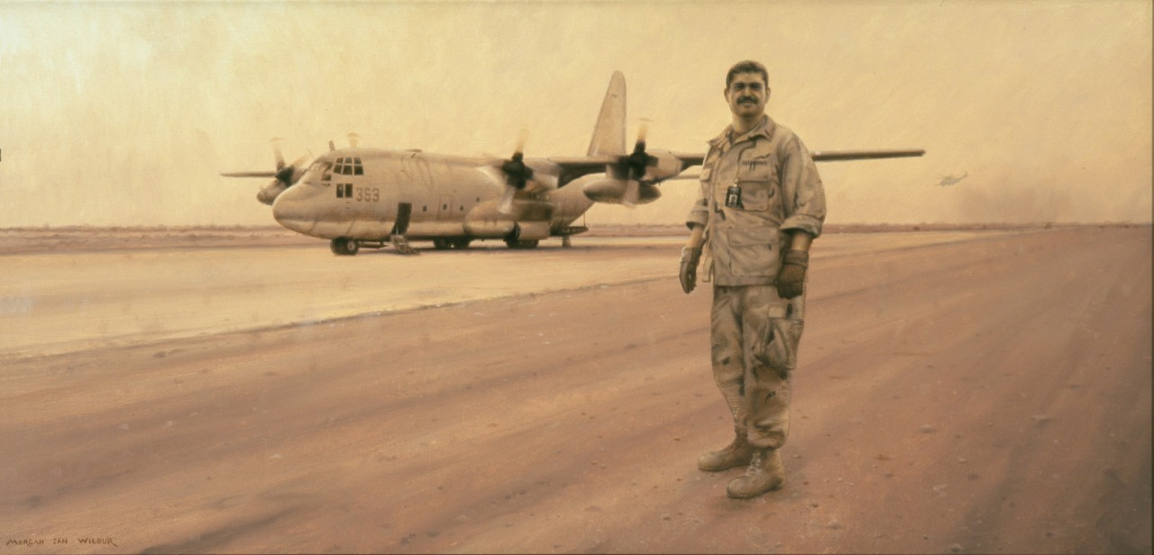 A man in uniform stands on the runway, in the background is a C-130 airplane. A sand storm is causing an orange light