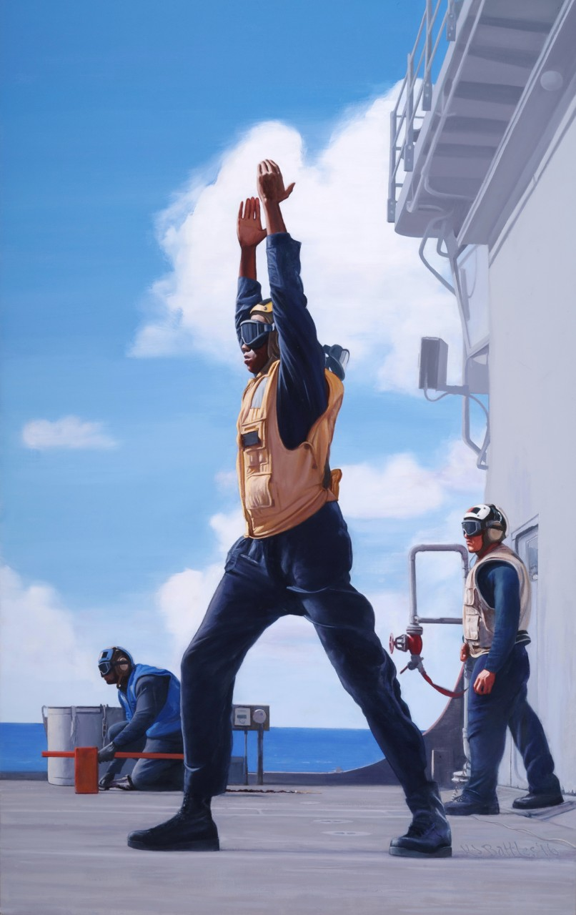 A crewmember on deck is signaling with his arms above his head