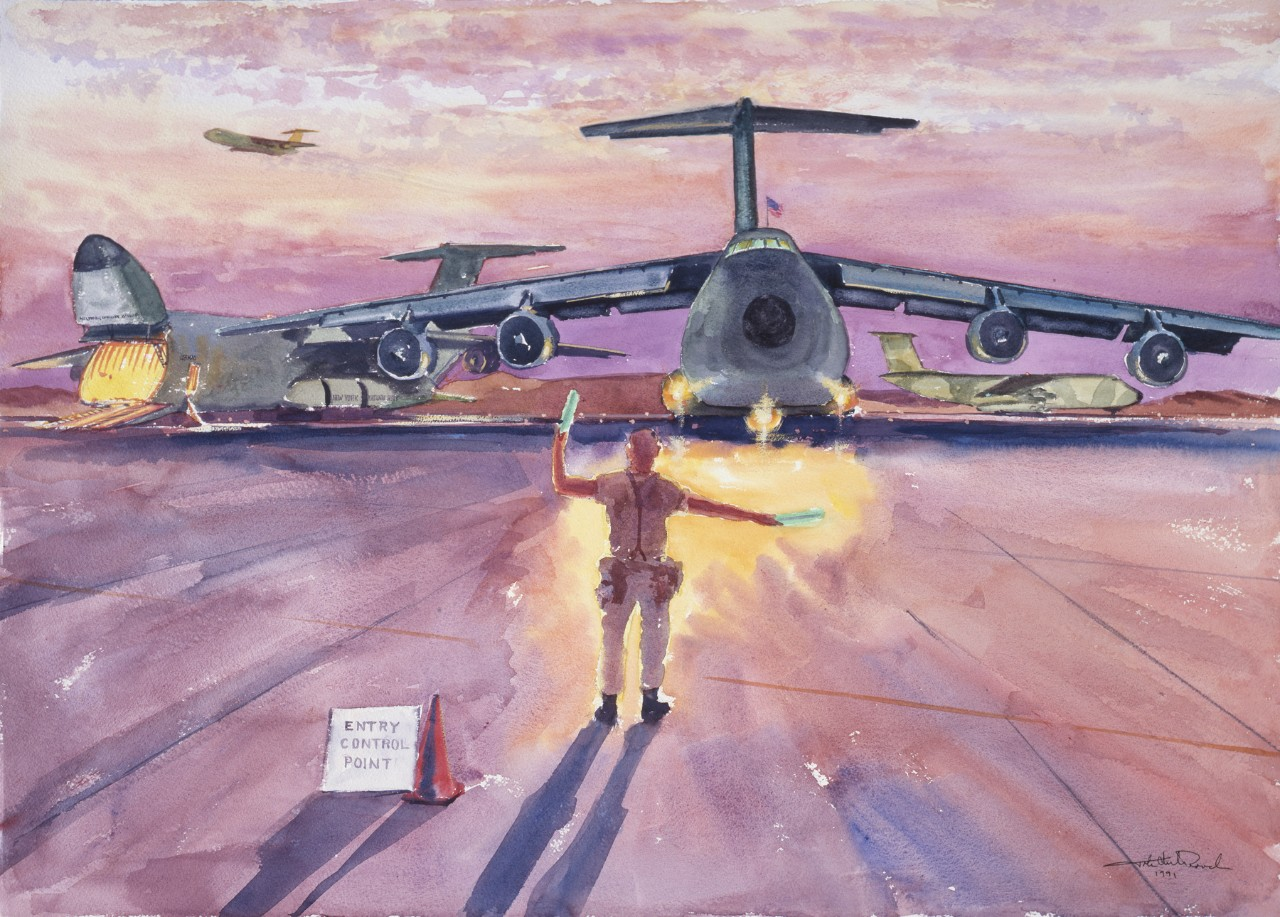 A marine directs a cargo plane at sunset, in the background are two other planes - the one on the left side has its nose open for unloading