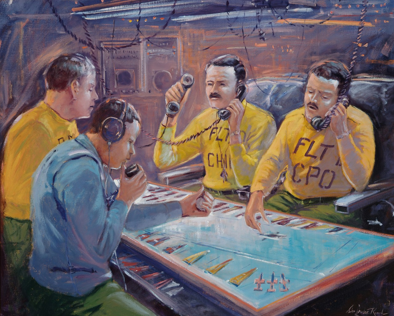 Four men at a table; three are wearing yellow shirts, two are talking into phones, one man wearing a blue shirt as a headset.