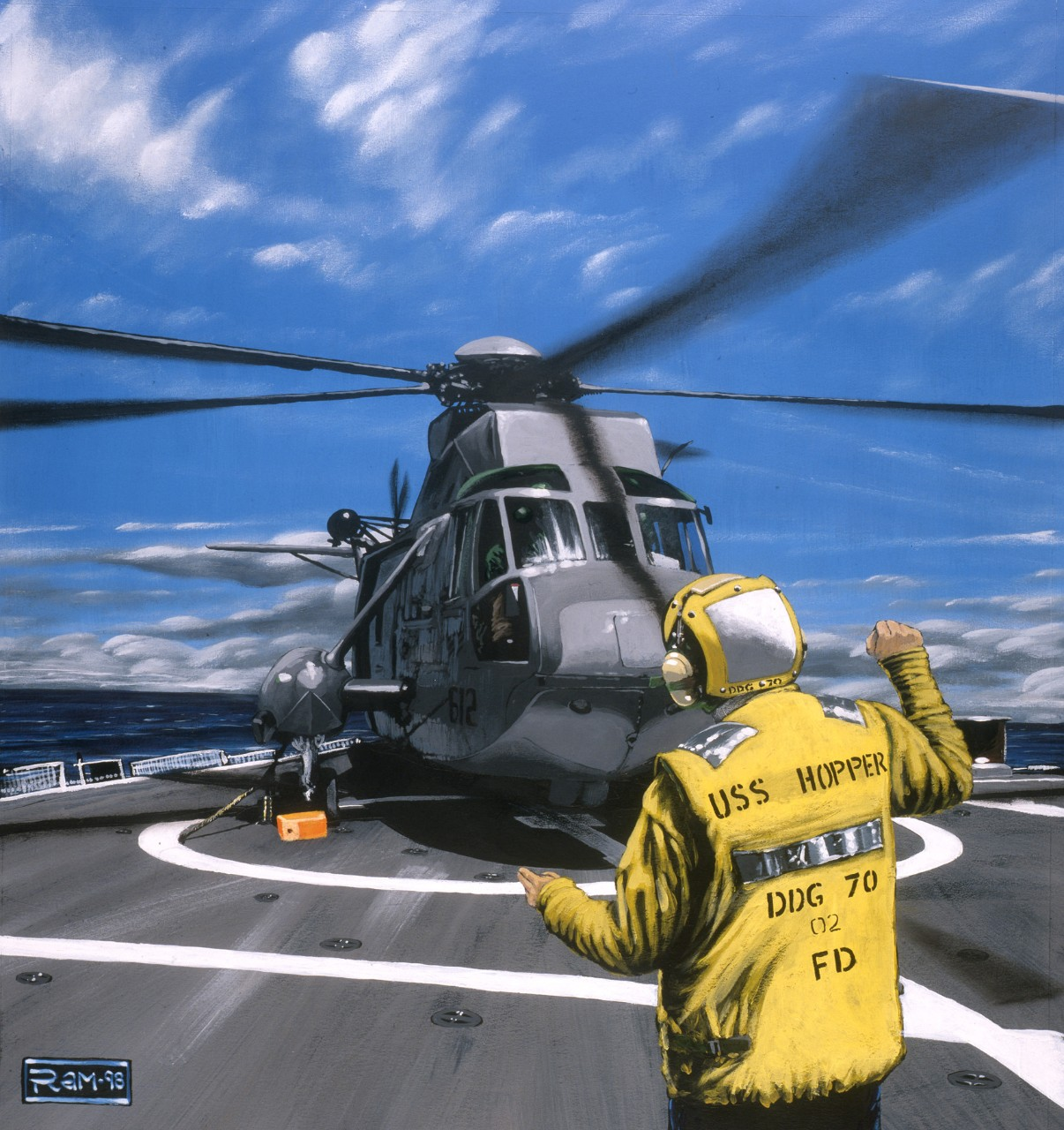 A crewman directs a helicopter on the landing pad