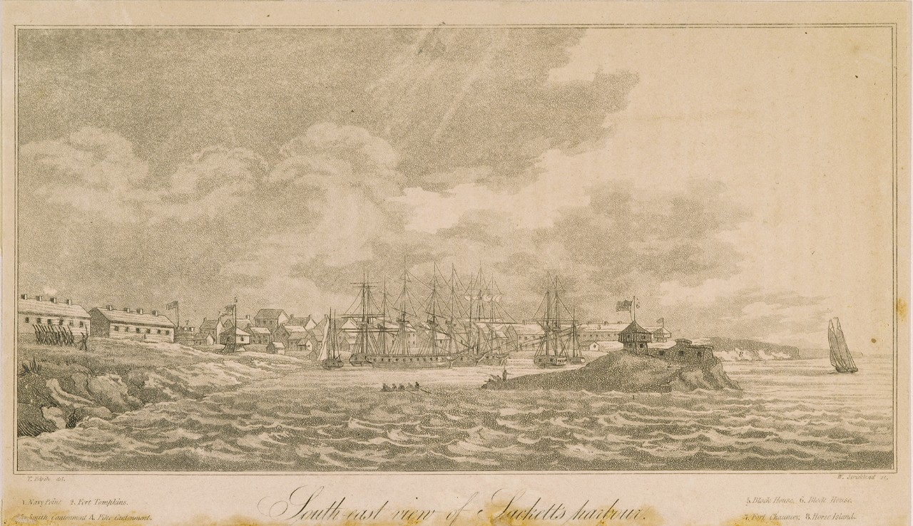 A view of a harbor with ships close to shore and buildings in the background. In the foreground is an island with a fort.