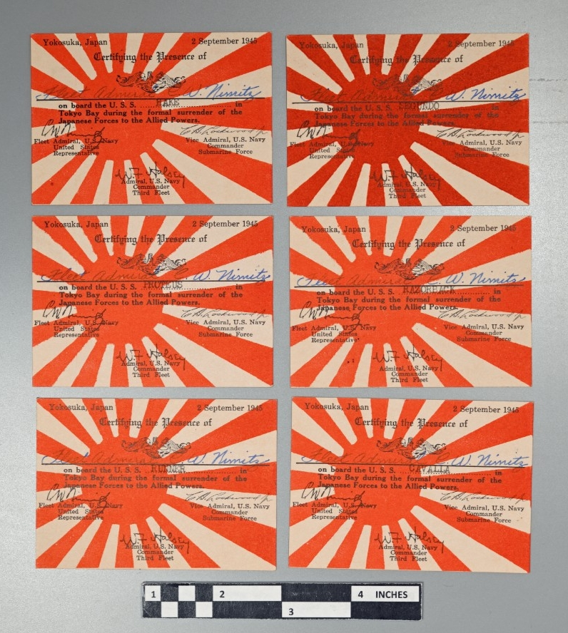 "<p>A group of seven small, 2.55"" x 3.54"" rectangular cards of white cardstock. The background of the obverse has a representation of the Imperial Japanese Navy ensign printed in red consisting of a disc offset to the left with rays radiating out from the disc. Overprinted in black ink in the upper half of the obverse is the following: Yokosuka, Japan / 2 September 1945 / Certifying the Presence of / (US submarine qualification badge) / _________ / on board the U.S.S. ………… in / Tokyo Bay during the formal surrender of the / Japanese Forces to the Allied Powers. Overprinted in black in the lower half of the obverse are three facsimile signatures with titles as follows: C.W. Nimitz / Fleet Admiral, U.S. Navy / United States / Representative // C.A. Lockwood Jr. / Vice Admiral, U.S. Navy / Commander / Submarine Force // W.F Halsey / Admiral, U.S. Navy / Commander / Third Fleet. Hand-written signatures in very faded ink are visible above the solid black line with ""C.A.Lockwood"" to the left and ""C.W.Nimitz"" to the right. Each card is stamped in black ink on the dashed line with the name of a different vessel in capital letters. Identical cards are marked in a similar manner for USS Proteus (AS-19), USS Cavalla (SS-244), USS Hake (SS-256), USS Razorback (SS-394), USS Segundo (SS-398), USS Tigrone (SS-419) and USS Runner (SS-476).</p>"