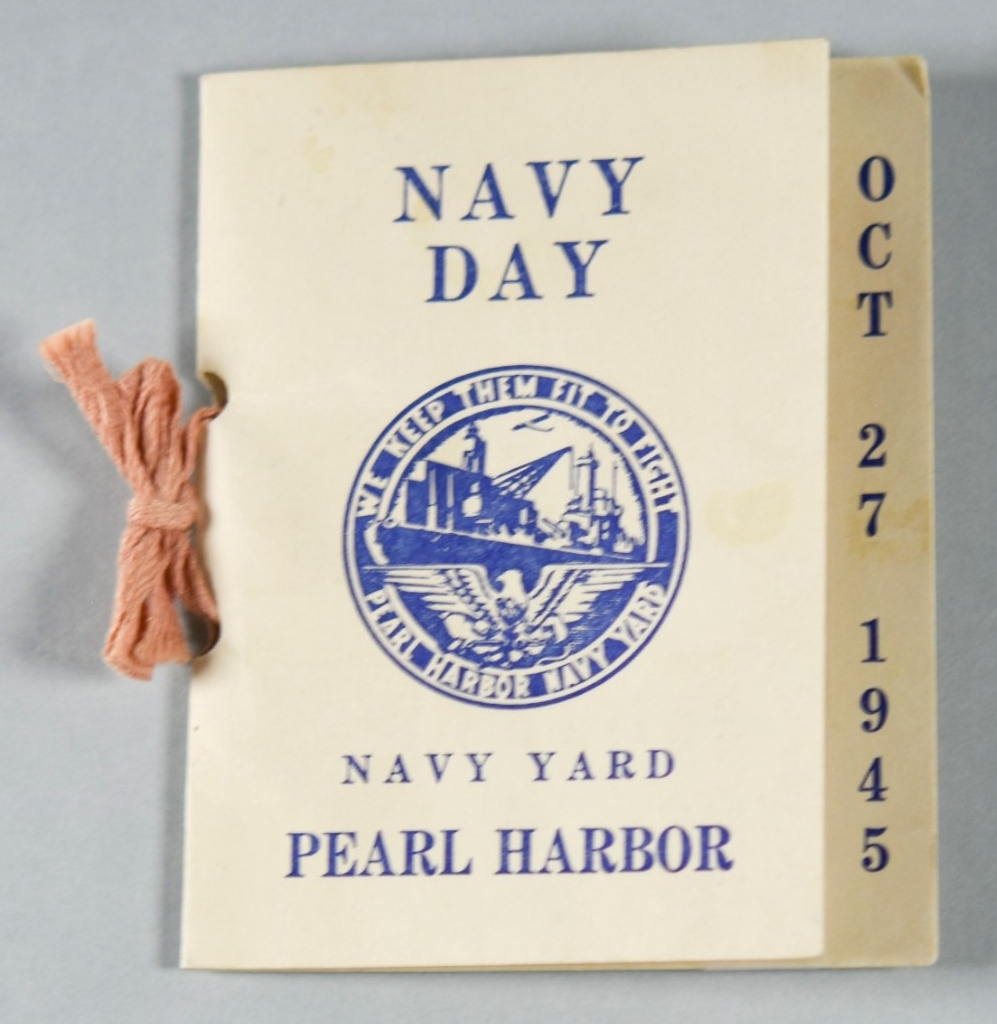 "<p>A 3.5"" x 4"" rectangle of white cardstock folded over to form a small souvenir card. The obverse reads: NAVY / DAY / NAVY YARD / PEARL HARBOR. A circular logo at the center of the obverse has lettering around the rim which reads: WE KEEP THEM FIT TO FIGHT / PEARL HARBOR NAVY YARD. </p>"