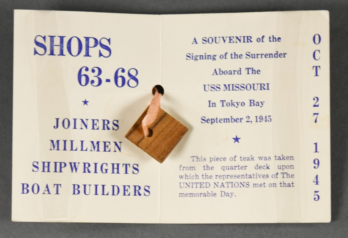 "<p>A 3.5"" x 4"" rectangle of white cardstock folded over to form a small souvenir card. The obverse reads: NAVY / DAY / NAVY YARD / PEARL HARBOR. A circular logo at the center of the obverse has lettering around the rim which reads: WE KEEP THEM FIT TO FIGHT / PEARL HARBOR NAVY YARD. Inside the card is a small square of brown teakwood with a hole drilled through it for the tape to pass through. &nbsp;</p> <div style=""left: -10000px; top: 0px; width: 9000px; height: 16px; overflow: hidden; position: absolute;""><div>&nbsp;</div> </div>"