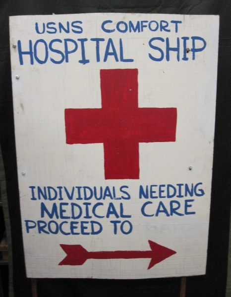 White wooden sign with blue lettering and a red cross and arrow directing for medical care