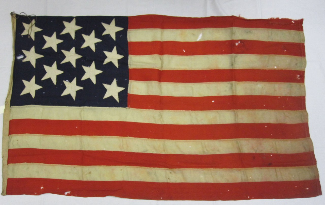 full view of Boat Flag from USS Olympia with 13 stars on a blue field and 13 stripes of red and white