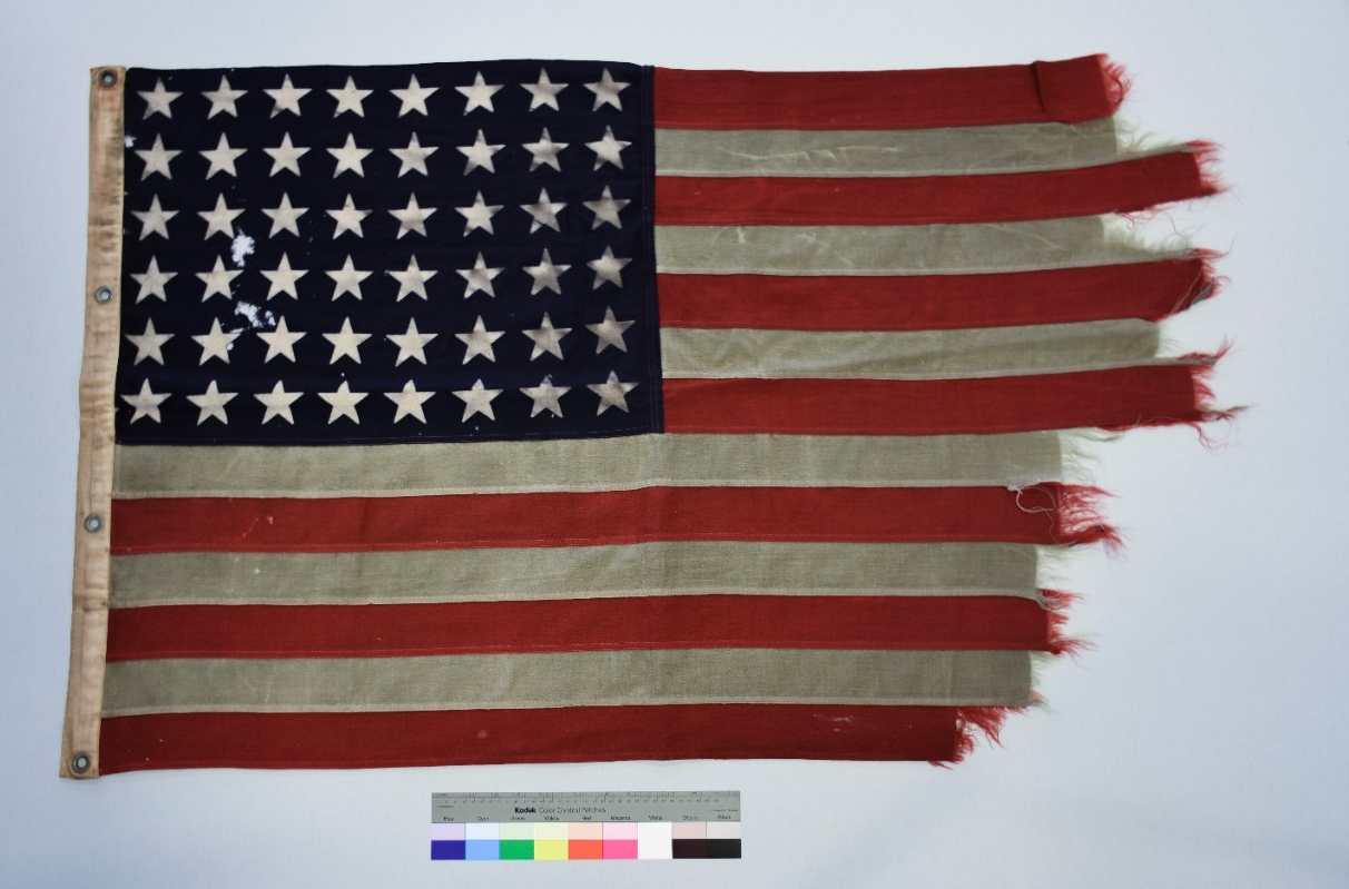 <p>Cotton flag canvas hoist heavy fraying and loss at fly. 48 stars on blue field at canton. 4 metal grommets</p>